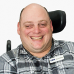 Photo of man in a grey shirt smiling.
