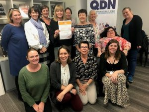 13 QDN staff standing looking at the camera with Paige holding the signed statement