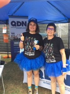 Alison and Lisa wearing blue tutu's with the QDN sign in the background