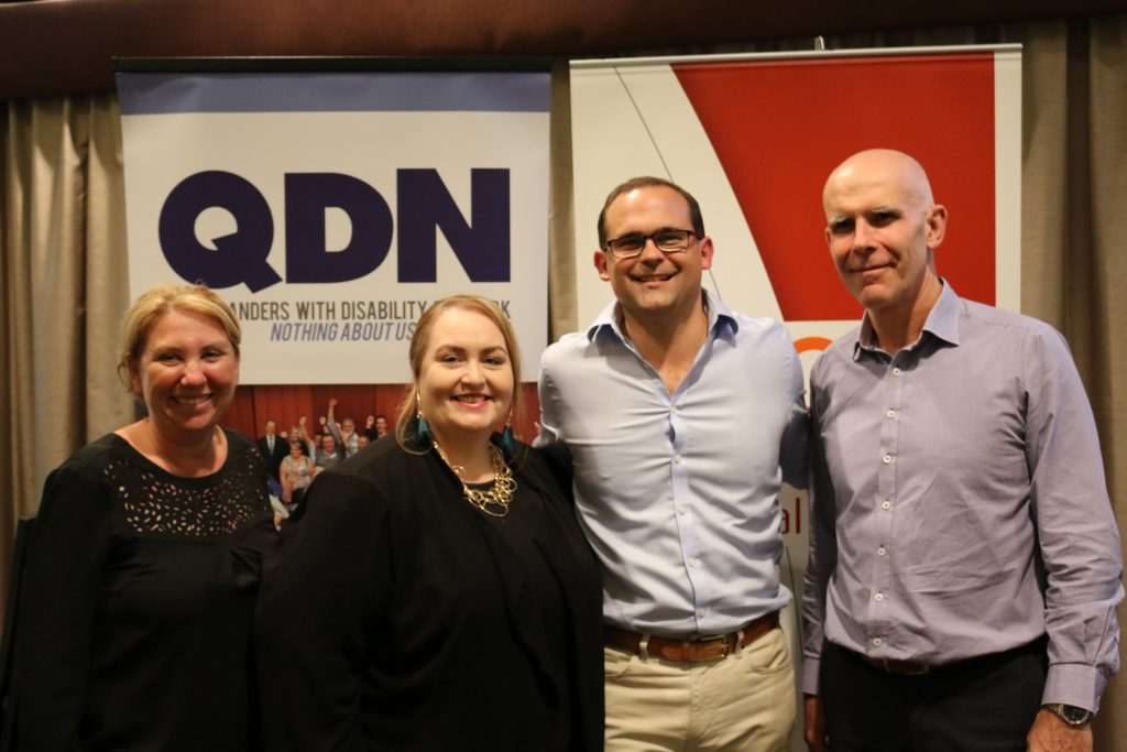 4 people standing smiling at the camera with QDN sign in the background