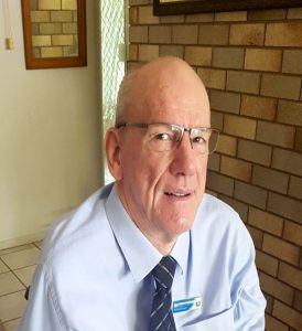 Man wearing glasses and a blue business shirt looking at the camera. There is a brick wall in the background.