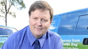 Photo of Paul Larcombe in a blue business shirt smiling at the camera. There is a van behind him.