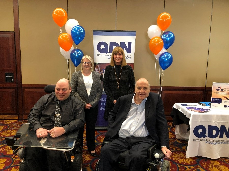 Photo of 4 people smiling at the camera with the QDN sign in the background the some orange, blue and white balloons.