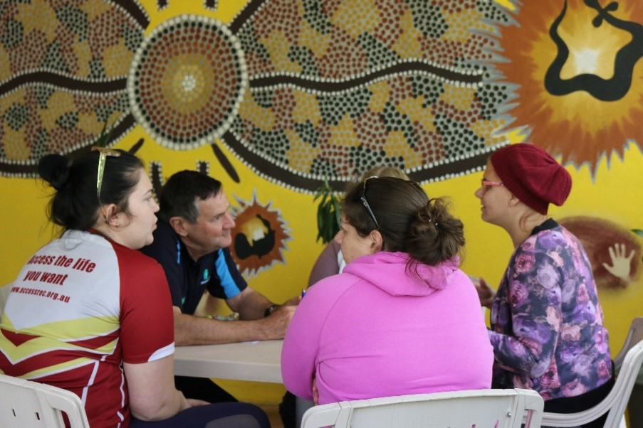 People talking at tables at the Disability Inclusion Disaster Risk Reduction in Rockhampton
