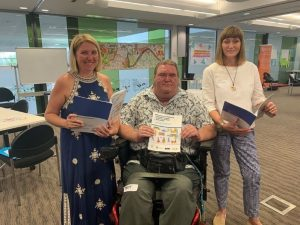 Michelle Moss, Matt McCracken and Paige Armstrong holding the Disability Inclusive Disaster Risk Reduction Framework and Toolkit