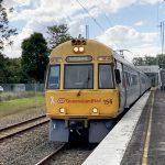 Yellow Queensland Rail train arriving at platform