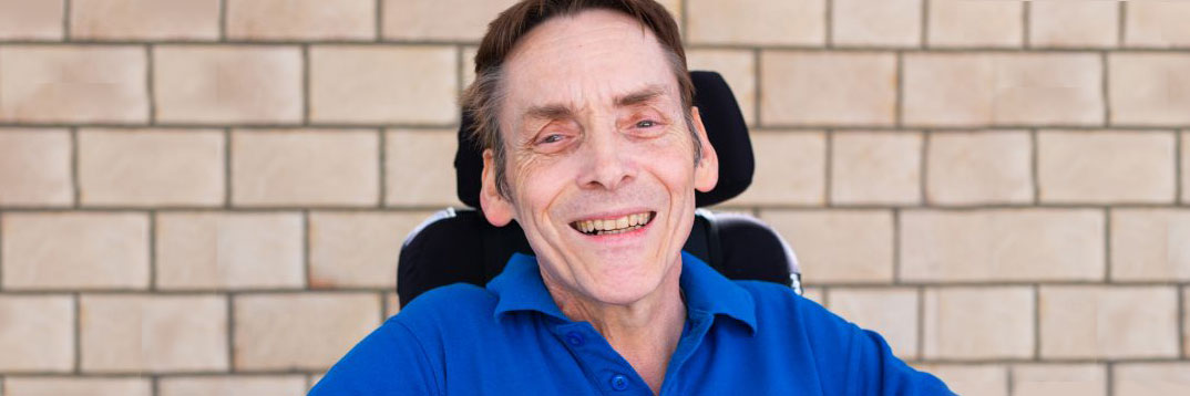 QDN board member Peter Tully is seated in a wheelchair wearing a blue polo and smiling at the camera.
