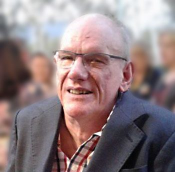 A photo of Des Ryan in a dark grey jacket and white shirt with red and blue stripes and wearing glasses.