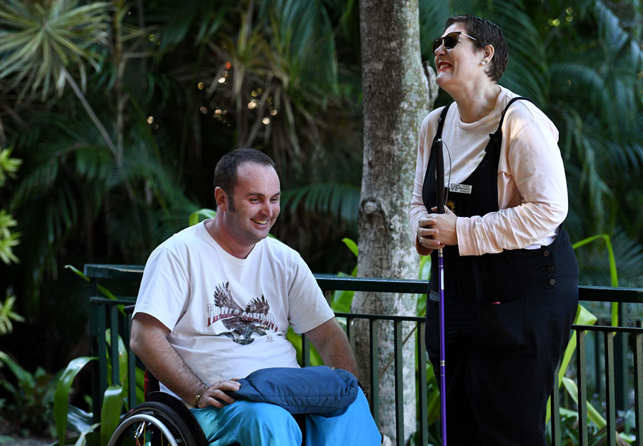 A man in a wheel chair and a lady with dark glasses and a cane laughing together.