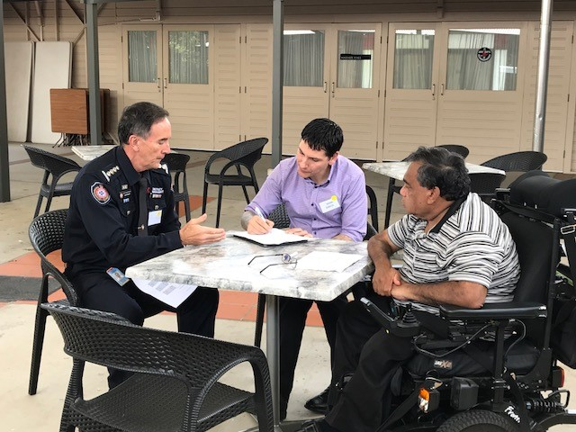 Three men sitting around a table, one in a emergency services uniform. One man taking notes and the man in the uniform is explaining something.