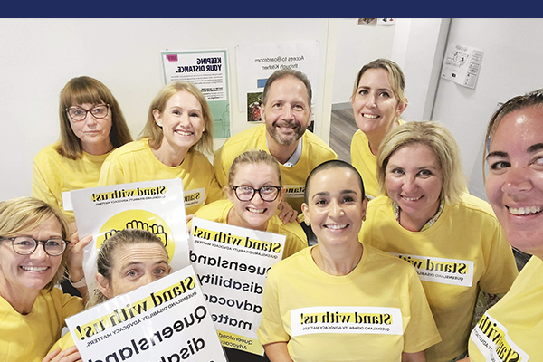 A group of men and women in yellow Stand with us Campaign shirts taking a group selfie.
