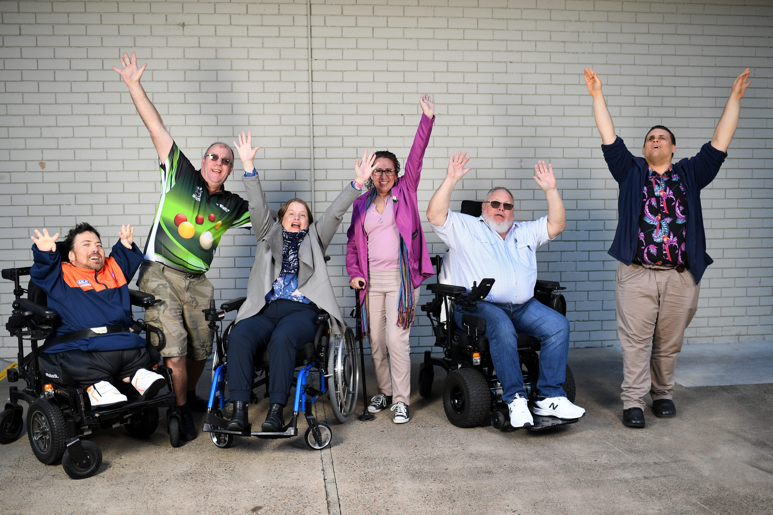 6 people with various disabilities stand in front of a brick wall with upraised arms