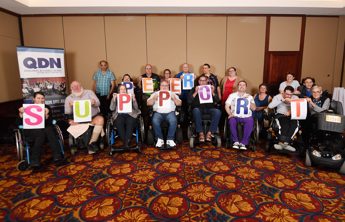 A group of people with disabilities in a room, each holding a letter that together reads Peer Support.