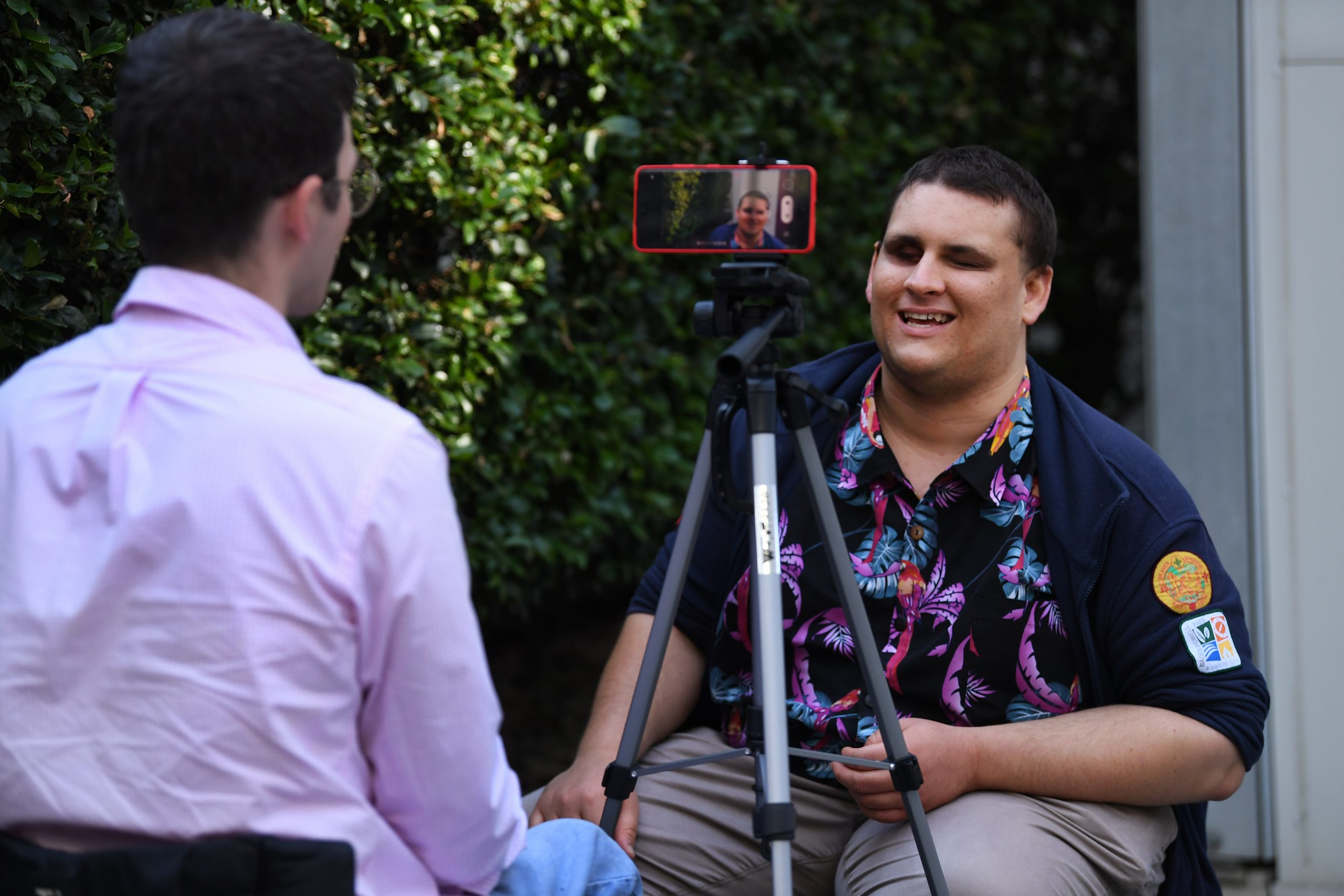 A man being interviewed and recorded on an iphone which is set up on a tripod.