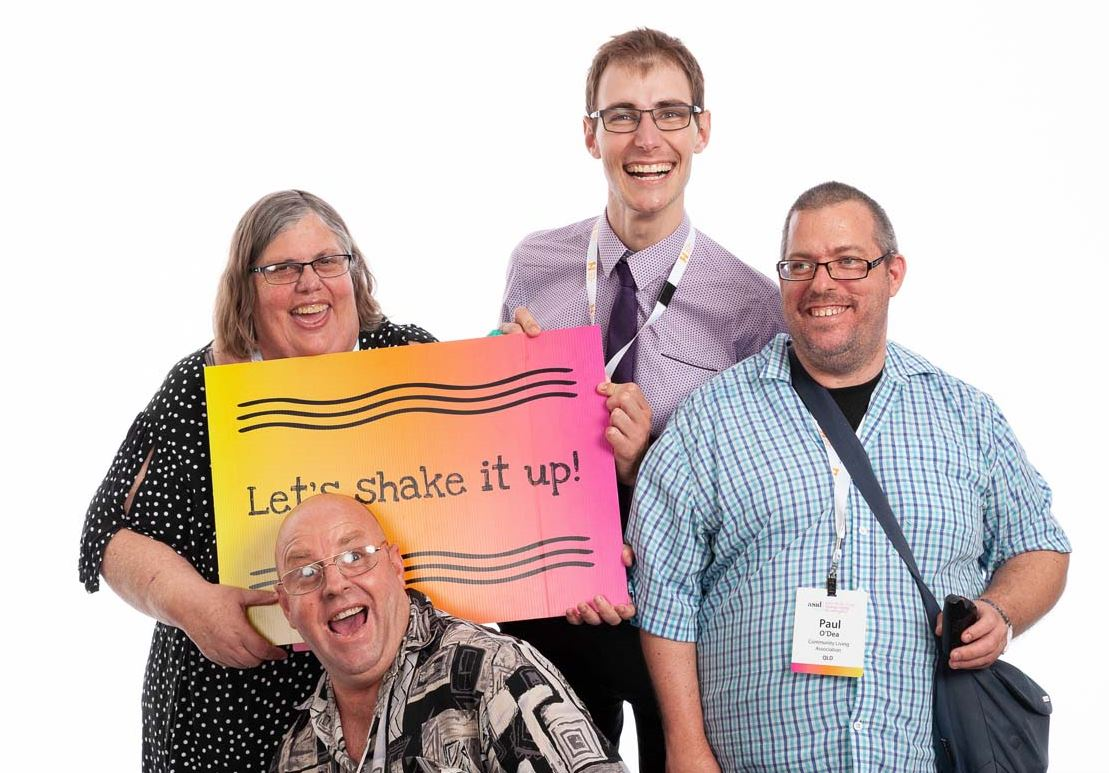 A group of happy smiling people holding a sign saying Let's shake it up!