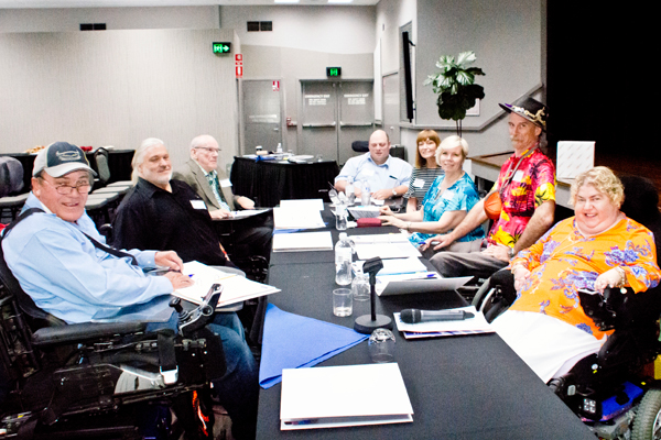 A group of eight people sitting around a table, some in wheelchairs