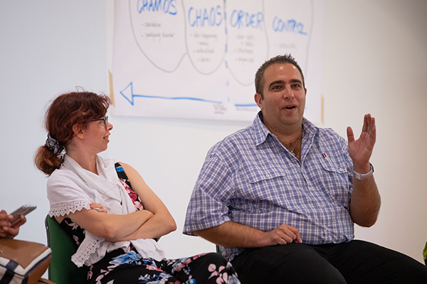 In front of a white board with diagrams, a man is speaking while a young lady smiles looking at him.