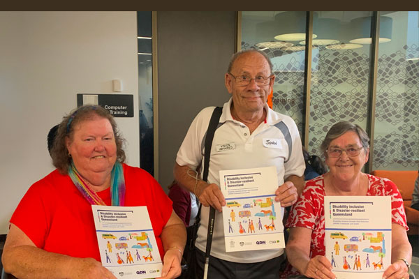 three people with disabilities holding up a QDN brochure about disability inclusive and disaster resilient Queensland.