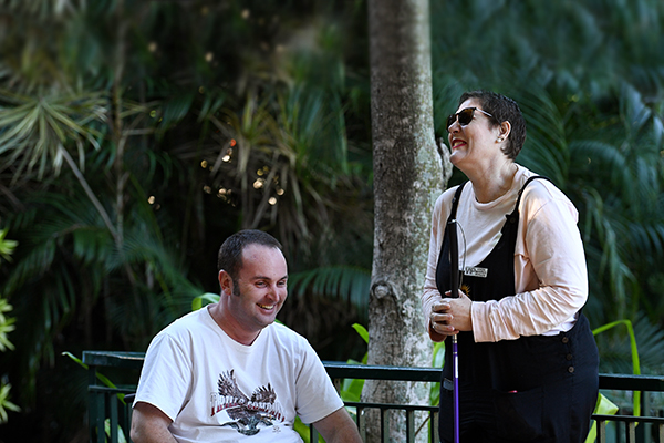 A man in a wheelchair and a woman standing holding a cane are outdoors laughing together.