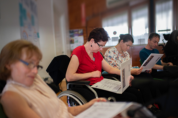 A row of people some in wheelchairs reading information in folders.