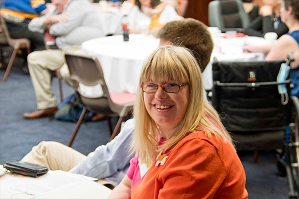 At a conference, a young woman with blonde hair and glasses wearing an orange top smiling brightly.