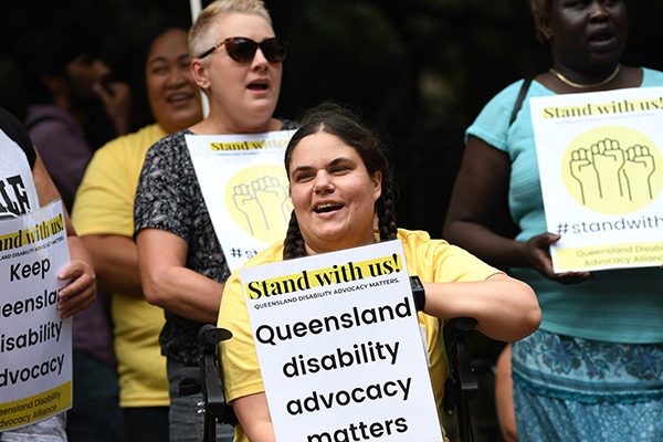A group of people at a rally with a young woman in the foreground holding a sign saying Stand with us! Queensland disability advocacy matters.