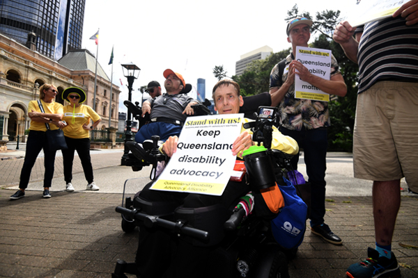Outdoors in a town square, an older man in a wheelchair is holding a sign saying Keep Queensland disability advocacy.