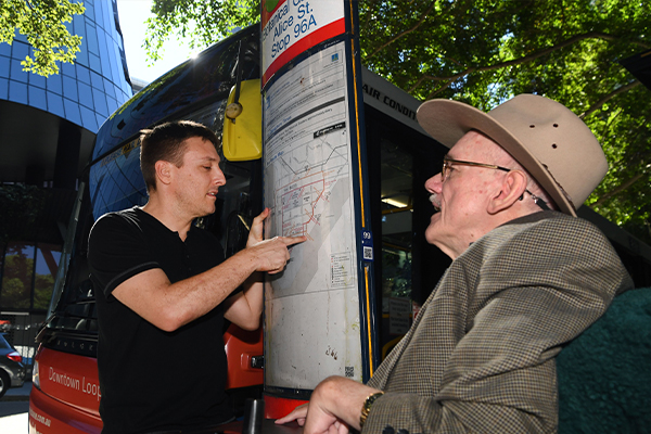 An elder man in a wheelchair speaks with a young man who is pointing at a sign with bus routes.