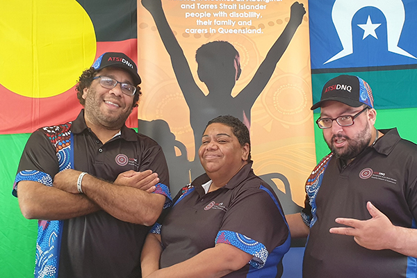 Three people standing in front of the Aboriginal and Torres Strait Island flags.
