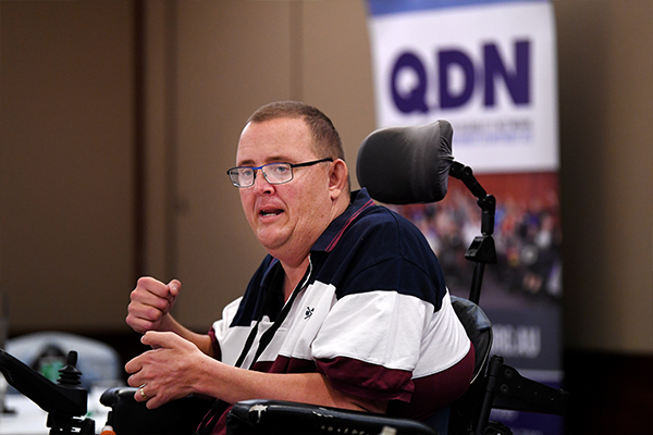 In a wheelchair a man is speaking with a QDN banner in the background.