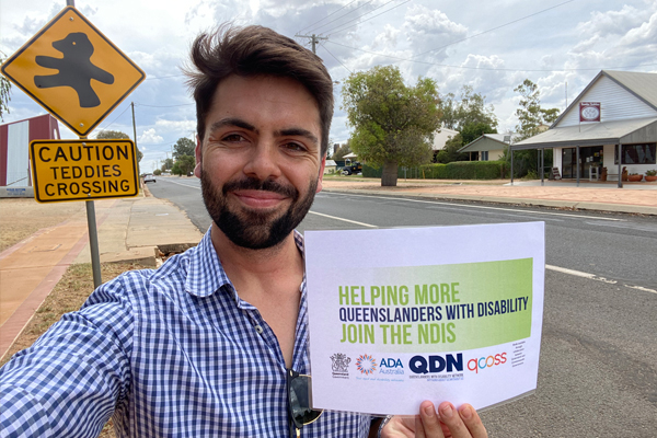 A young man outside in a suburban street holding a sign saying helping more Queenslanders with disability join the NDIS.