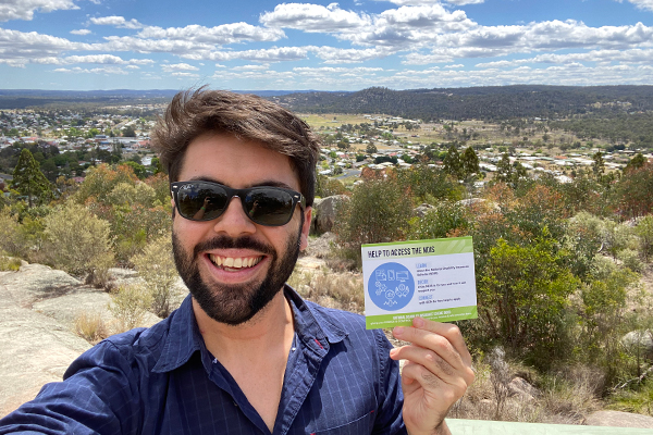 A young man wearing sunglasses stands outdoors with a long range view behind him. He is smiling and holding a card that reads Help to access the NDIS.