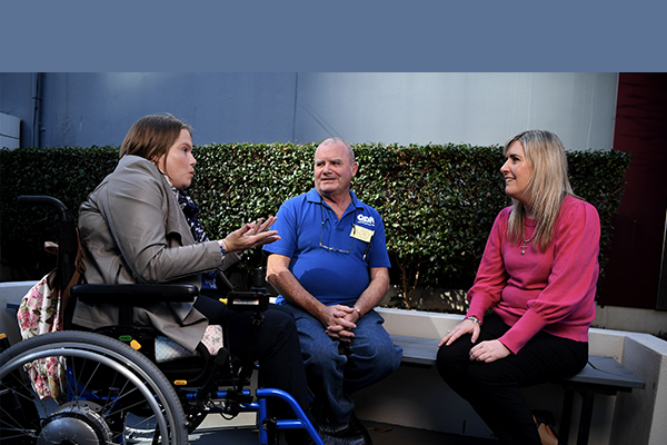 A young woman in a wheelchair speaking to a man wearing a blue QDN shirt and a young woman in a bright pink top.