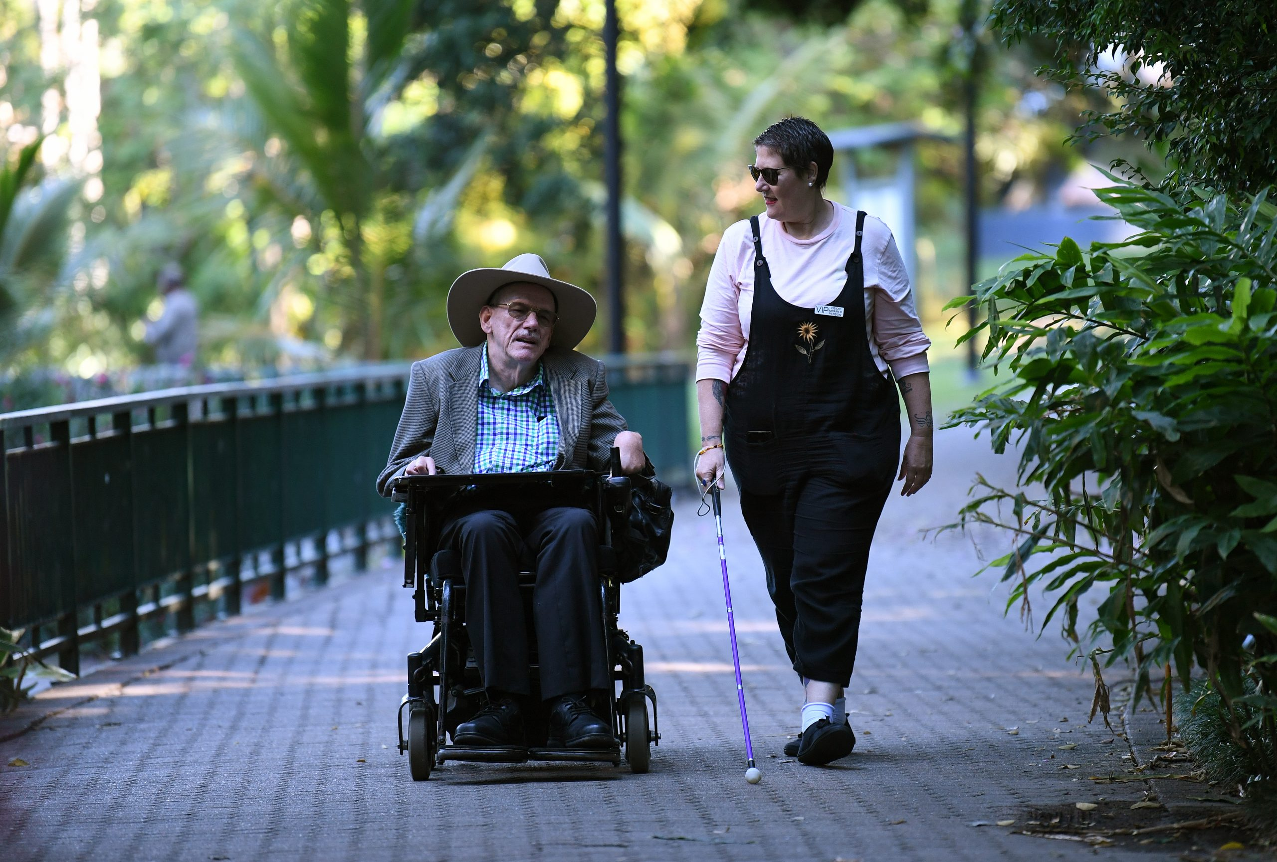 Outdoors, a man in a wheelchair chats with a blind lady walking next to him.