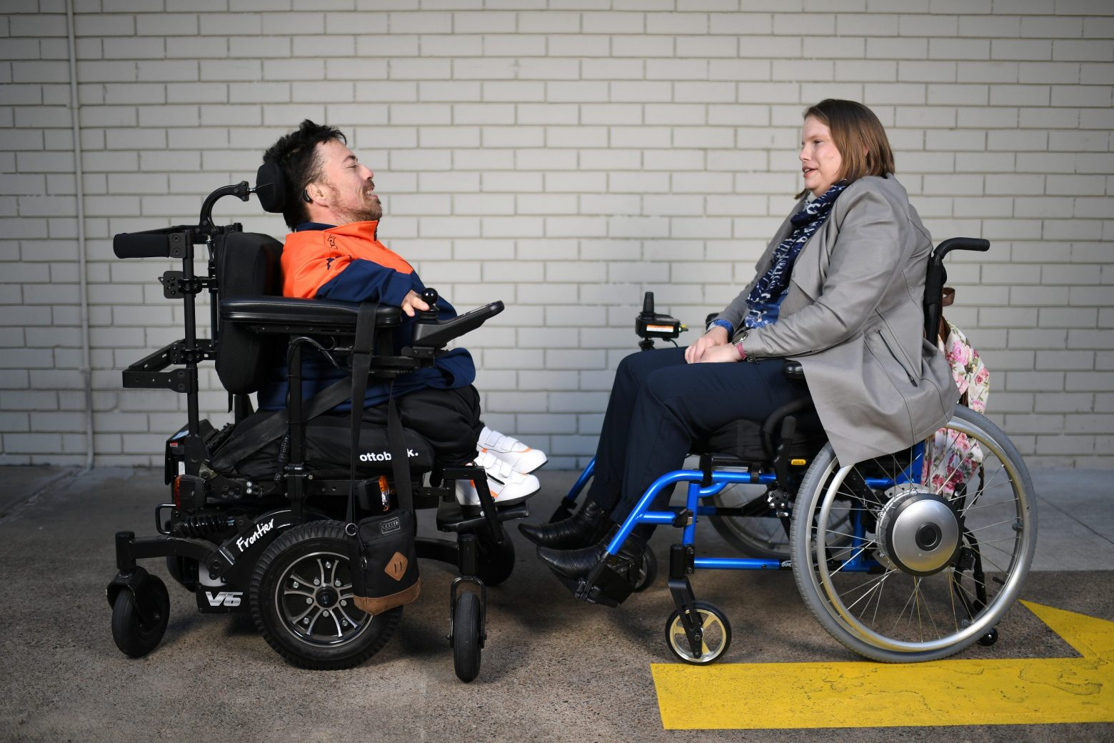 A man and a woman, both in wheel chairs facing each other talking, in front of a white brick wall and there is a bright yellow painted arrow on the ground,