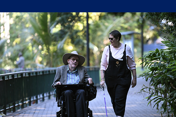 Two people chatting outdoors, one in a wheelchair, the other with a cane.