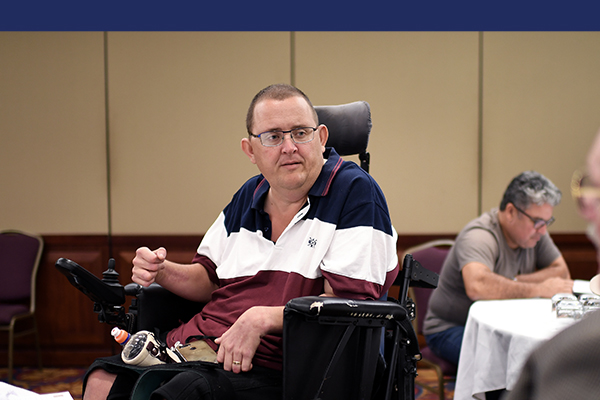 A man wearing a blue, white and maroon striped shirt with glasses in an electric wheelchair