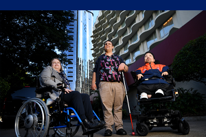 A lady in a wheel chair next to a man holding a white cane and another man in a wheel chair next to him.