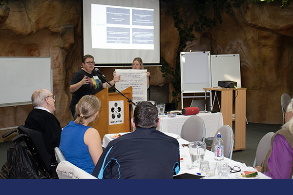 The back of a bunch of people at a workshop listening to a speaker at the lectern at the front of the room talking into a microphone. There is an over head projector image of notes on the wall behind the speaker.