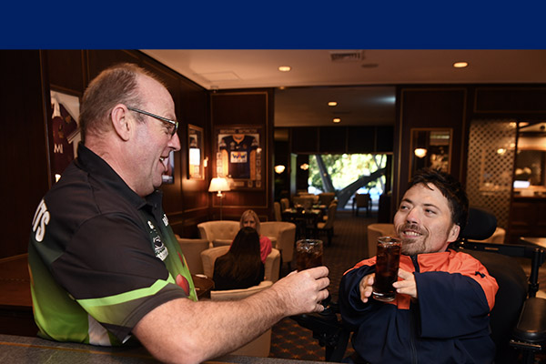 Two men having a drink. The man on the right is in a wheel chair and wearing a blue and orange shirt and the man on the left is wearing a black and green branded shirt. They are in a bar lounge.