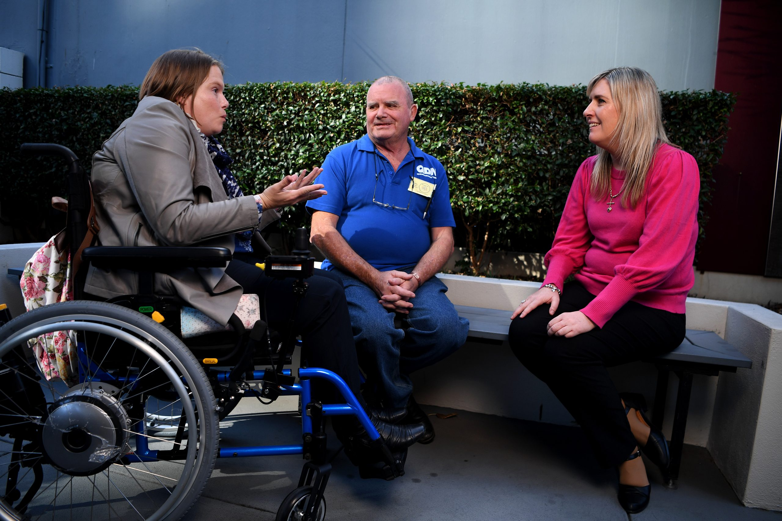 A woman in a wheelchair is holding her arms out in expression, and talking towards another man and woman who are seated on a bench in front of a bush and are looking at her.