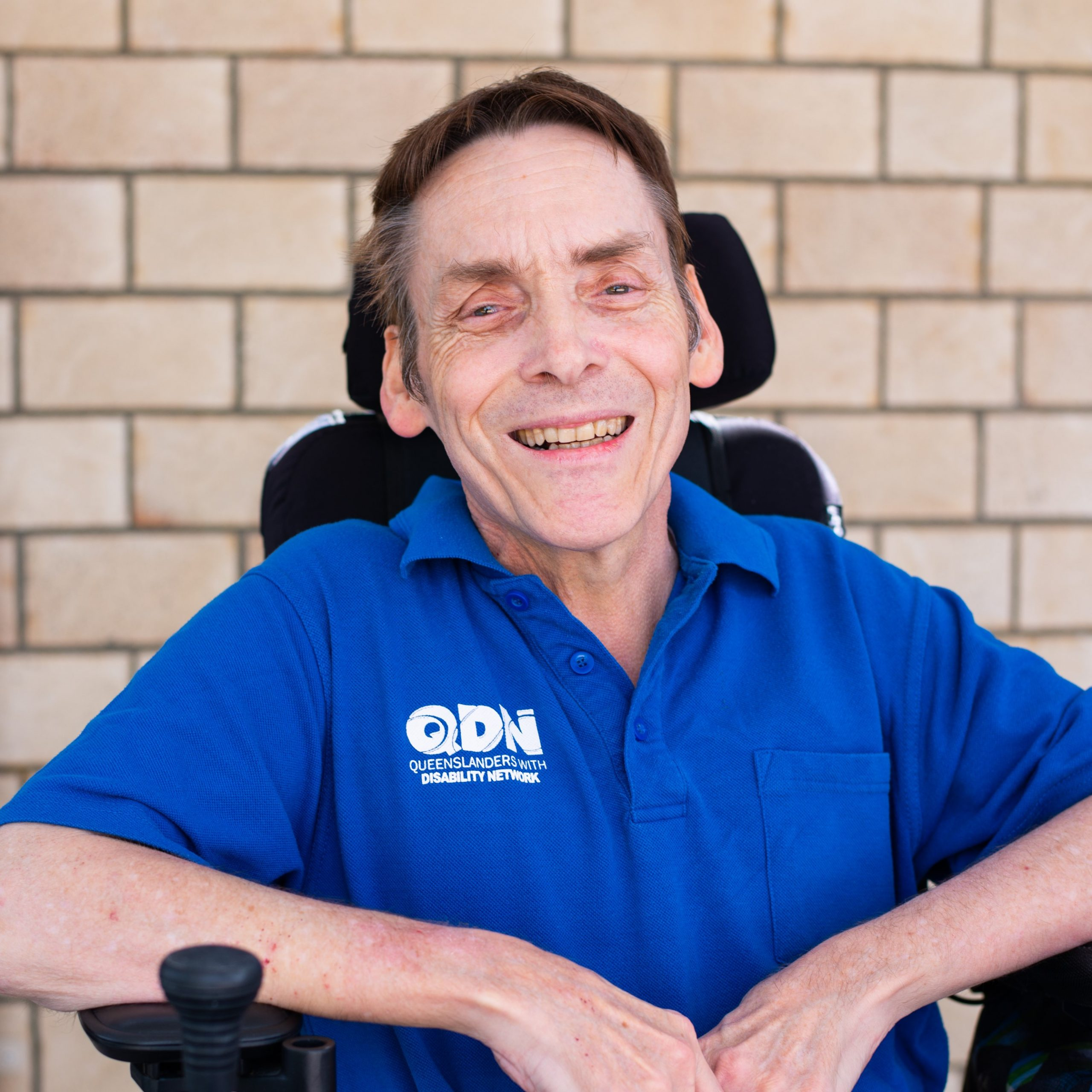 A photo of board member Peter Tully, wearing a blue QDN polo and smiling at the camera.