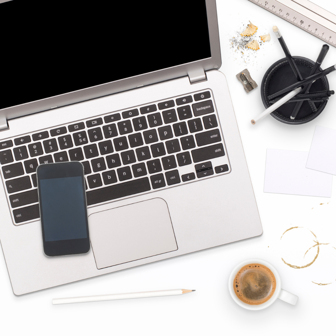 A photo of a laptop with a phone sitting on the keyboard, there are pencils in a holder and a coffee mug with coffee in it.