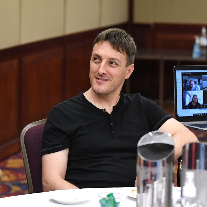 A young man smiling wearing a black shirt listening at a conference.