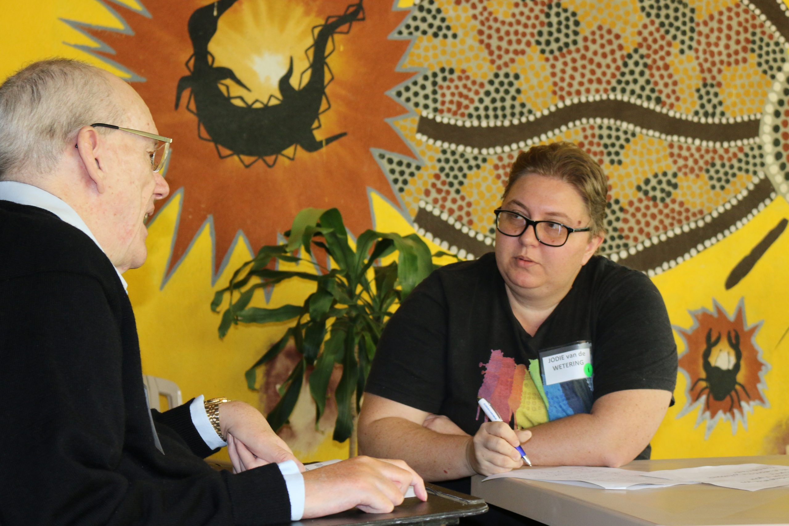 A man and a woman talking at a desk in front of a wall with Indigenous Australian art on it.