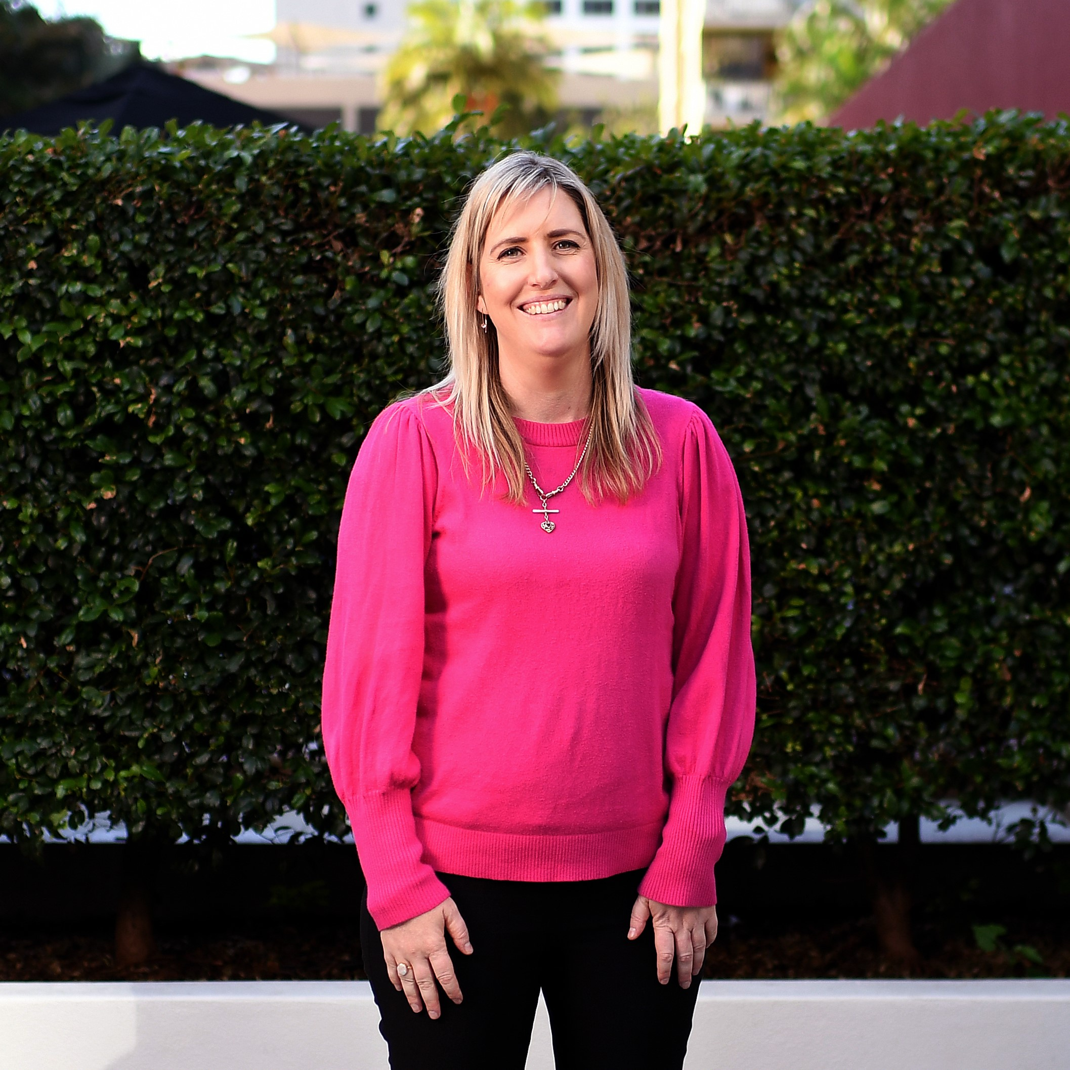 A woman with long blonde hair wearing a bright pink long sleeved top and black pants, smiling at the camera.