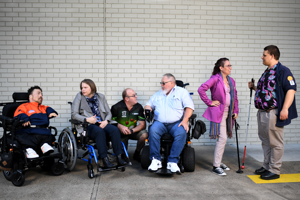 Three people in wheelchairs, two people standing and one man crouching down, are all talking together in front of a brick wall.