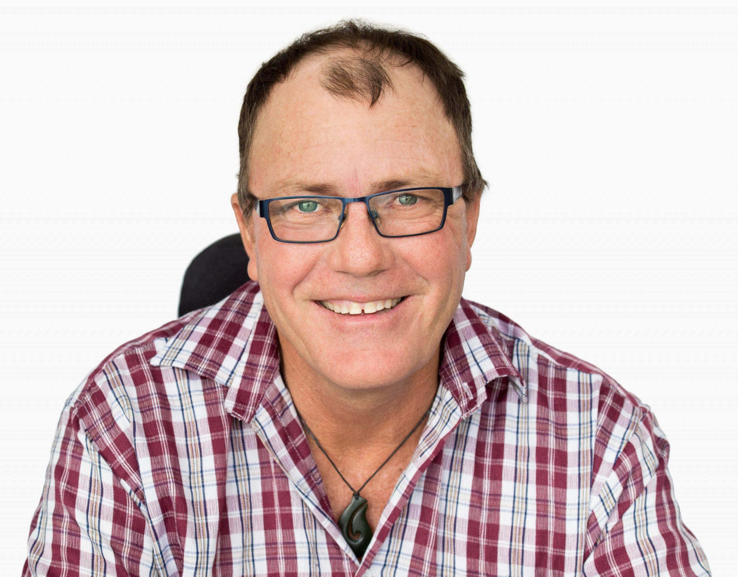 man with glasses and a checkered shirt smiling at camera