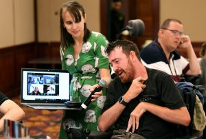A man in a wheelchair is speaking into a microphone being held by a lady in a green dress. She is also holding a laptop that has four faces on it, of people participating in a Zoom call.