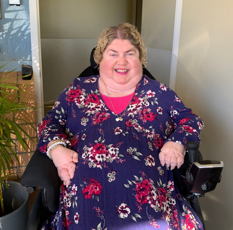 A lady in a blue dress with pink flowers in a wheel chair smiling at the camera.